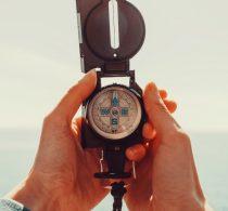 Hände eines älteren Mannes, mit dem Kompass auf das Meer blickend.
