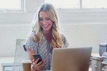 Attractive woman working on a laptop computer. She is casually dressed  with long blonde hair. She looks relaxed with a cup of coffee and she is probably surfing the internet. She could be a business woman working at home or in an office. Shot is back lit with copy space. There is a digital tablet and she is texting on a smart phone.