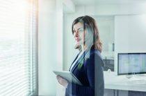 Deutschland, Wiesbaden, Business, Büro, Businessfrau, Geschäftsfrau mit Tablet-Computer schaut aus dem Fenster