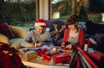 Young couple at home with their pet dog at Christmas time. They are writing out cards and wrapping presents together.